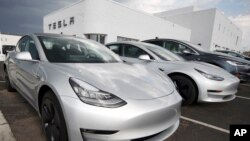 In this July 8, 2018, file photo, 2018 Model 3 sedans sit on display outside a Tesla showroom in Littleton, Colo. (AP Photo/David Zalubowski, File)