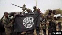 Des soldats nigérians tiennent un drapeau Boko Haram saisi dans la ville a récemment repris de Damasak, Nigeria, 18 mars 2015