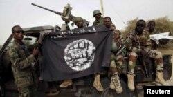 Soldados del ejército de Nigeria sostienen una bandera del grupo armado Boko Haram, después de los operativos contra los extremistas.