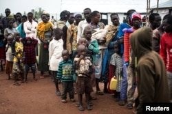 FILE - South Sudanese people wait at a transit centre in Koluba before boarding courtesy buses to Imvepi refugee settlement camp in Arua District, northern Uganda, Aug. 12, 2017.