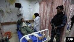 Một sĩ quan cảnh sát canh gác cạnh đồng nghiệp bị thương trong bệnh viện ở Baghdad sau vụ đánh bom