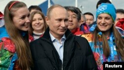 Russian President Vladimir Putin (C) and Olympic Village Mayor Elena Isinbaeva (R) visit the Coastal Cluster Olympic Village ahead of the Sochi 2014 Winter Olympics at the Athletes Village in Sochi, Feb. 5, 2014.
