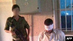 Bức ảnh của tổ chức Breaking the Silence đưa ra hôm 18 tháng 8, 2010 cho thấy một binh sĩ Israel (có lẽ là Eden Aberjil) đứng chụp ảnh cạnh một tù nhân người Palestine