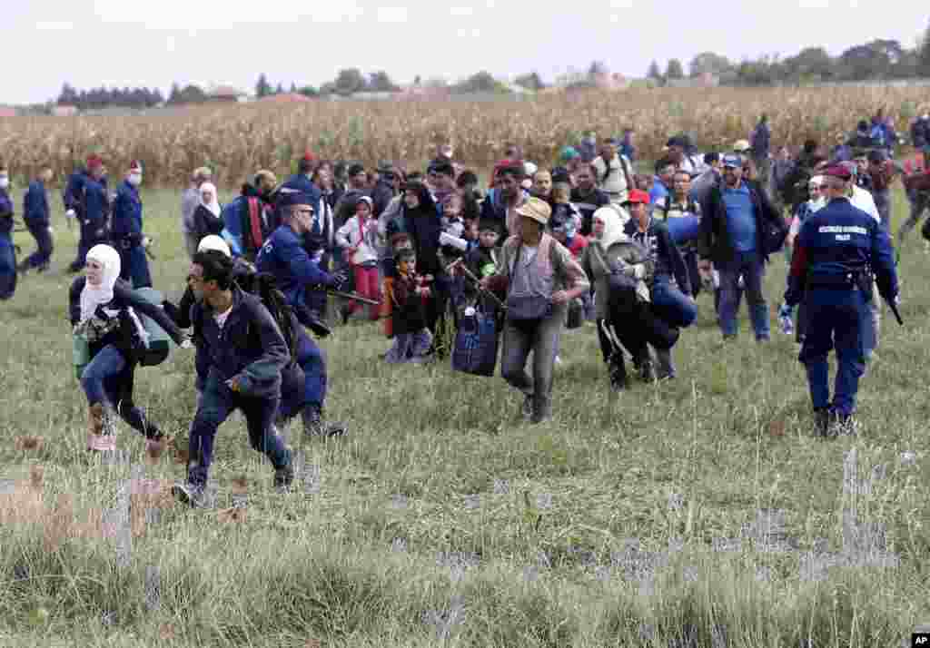 Migrants run away from a temporary holding center for asylum seekers in Roszke, southern Hungary, Sept. 8, 2015. Hungarian police struggled to control thousands of migrants hopping cross-border trains into Austria, taking advantage of country's surprise decision to stop screening international train travelers for travel visas, a get-tough measure that the country had launched only days before to block their path to asylum in Western Europe.