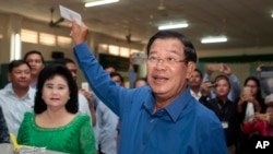 FILE - Prime Minister Hun Sen of the Cambodian People's Party shows off his ballot paper before voting in local elections at Takhmau polling station in Kandal province, southeast of Phnom Penh, June 4, 2017.