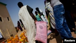 FILE - A man walks away with a bag of rice at a food distribution center run by the Spanish NGO Accion Contra el Hambre (Action Against Hunger) in Tarenguel, Mauritania, May 30, 2012.
