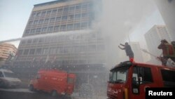 Firefighters put out a fire at the Duroy hotel following a bomb attack, in Raouche, in western Beirut, June 25, 2014.