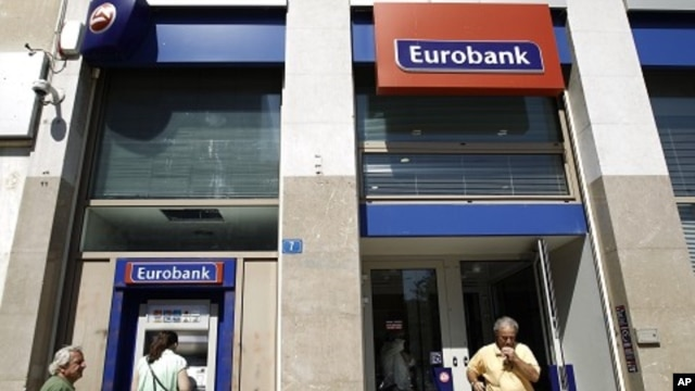 A woman makes a transaction at an ATM of a Eurobank branch in Athens September 23, 2011.