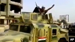 FILE - This image taken from video shows an Islamic State militant waving upon his arrival in Beiji, north of Baghdad, June 17, 2014.