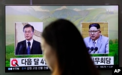 A woman walks past a TV screen showing file footage of South Korean President Moon Jae-in, left, and North Korean leader Kim Jong Un, right, during a news program shown at the Seoul Railway Station in Seoul, South Korea, March 29, 2018.