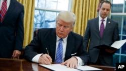 Donald Trump signe l'acte de retrait des Etats-Unis du traité de libre-échange transpacifique (TPP), Washington, le 23 janvier 2017