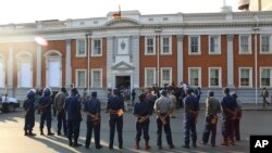 FILE: Police gather outside the Constitutional Court after the court upheld Zimbabwean President Emmerson Mnangagwa' s narrow victory in Harare, Friday, August, 24, 2018. Zimbabwe's constitutional court on Friday unanimously upheld President Emmerson Mnangagwa's narrow victory.