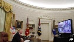 El presidente Donald Trump saluda a miembros de las cinco ramas del ejército, a través de una videoconferencia, el día de Navidad, el martes 25 de diciembre de 2018.
