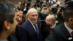 FILE - Mikhail Khodorkovsky (C) arrives at his first news conference after his release in Berlin, Germany, Dec. 22, 2013.