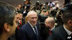 FILE - Mikhail Khodorkovsky, center, is seen arriving at his first news conference after his release in Berlin, Dec. 22, 2013.