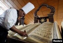Seorang chef Indonesia memberikan sentuhan akhir pada kue berbentuk Al-Quran raksasa untuk sebuah hotel di Jakarta, 9 Oktober 2005. (Foto: dok).