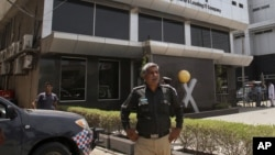 Pakistani police officer stands guard at the office of Axact software company in Karachi, May 27, 2015.