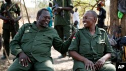 FILE - South Sudan's rebel leader Riek Machar (L) and his wife Angelina Teny joke in front of their tent in a rebel-controlled area in Jonglei State, South Sudan, Jan. 31, 2014.