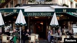 Pelanggan duduk di teras kafe dan restoran Les Deux Magots di Paris yang dibuka kembali setelah tutup selama berbulan-bulan di tengah pandemi COVID-19 di Perancis, 19 Mei 2021. (REUTERS / Christian Hartmann)