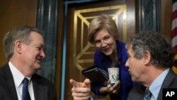 지난 2월 미 상원 금융위원회의 마이클 크라포 위원장(왼쪽부터), 엘리자베스 워런 상원의원, 셰러드 브라운 상원의원이 청문회에서 대화하고 있다.