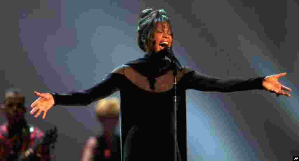 """Whitney Houston performs during the 21st annual American Music Awards at the Shrine Auditorium Feb. 7, 1994 in Los Angeles. On the strength of """"The Bodyguard"""" soundtrack, the vocalist swept the awards with seven honors and also was named recipient of the"""