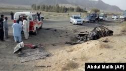 Des bénévoles se tiennent devant un véhicule où se trouvait mollah Akhtar Mansour, dans la région de Baluchistan, une province du Pakistan, près de la frontière de l'Afghanistan, le 21 mai 2016.