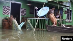 A woman tries to get on a boat from her house half-submerged in Daga township, Ayeyarwaddy division, about 126 kilometers (78 miles) northwest of Rangoon, Burma, August 24, 2012.