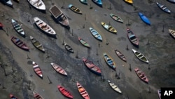 Small boats sit on the shore of Guanabara Bay in the suburb of Sao Goncalo, across the bay from Rio de Janeiro, Brazil.