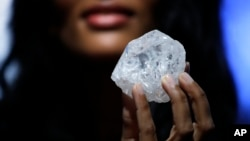 A model displays a large diamond at Sotheby's in New York, May 4, 2016. A 3-billion-year-old diamond the size of a tennis ball — the largest discovered in over a century — could sell for more than $70 million, auctioneer Sotheby's said Wednesday.