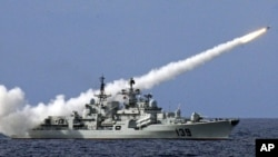 FILE - A Chinese warship launches a missile during a live-ammunition military drill in the South China Sea.