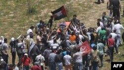 Пропалестинские демонстранты выносят убитого из пограничной зоны между Сирией и Израилем на Голанских высотах. 5 июня 2011 года