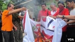 """Kelompok Front Pancasila membakar lambang PKI di halaman Ismail Marzuki, sebagai bentuk penolakan simposium bertajuk """"Membedah Tragedi 1965."""" (VOA/Fathiyah Wardah)"""