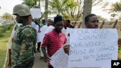 Protesters walk past a soldier standing guard during a rally against the decision to end fuel subsidies in Nigeria's capital Abuja, January 6, 2012.