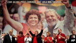 FILE - Brazil's President Luiz Inacio Lula da Silva, center, raises arms with his Chief of Staff Dilma Rousseff at an annual Workers Party Congress in Brasilia, Brazil, where the party announced Rousseff as the party's 2010 presidential candidate, Feb. 20