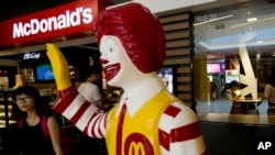 FILE- A customer walks past a statue of Ronald McDonald on display outside a McDonald's restaurant in Beijing.