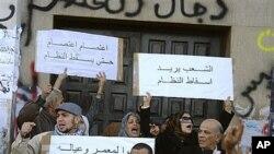 """利比亞抗議者高舉標語牌。左上方的標語﹕""""罷工﹐直到這個政權垮臺為止。"""