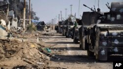 Iraqi security forces surround the government complex in central Ramadi, 70 miles (115 kilometers) west of Baghdad, Iraq, Monday, Dec. 28, 2015. (AP Photo)