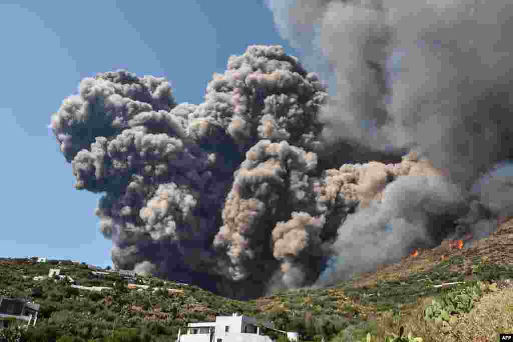 Smoke billows and flames propagate across the hillside near houses after the Stromboli volcano erupted, July 3, 2019, on the Stromboli island, north of Sicily.