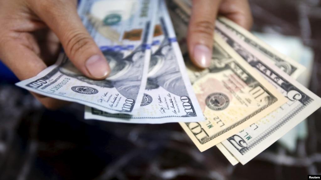 Một nhân viên ngân hàng đếm các đồng đôla Mỹ ở Hà Nội.
