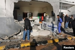 FILE - Civilians and security personnel survey the scene of an explosion at a police station in Tripoli, Libya, a blast later claimed by militants professing loyalty to the Islamic State, March 12, 2015.