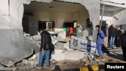 FILE - Civilians and security personnel stand at the scene of an explosion at a police station in Tripoli, Libya, a blast later claimed by militants professing loyalty to Islamic State, March 12, 2015.