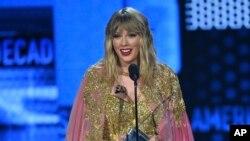 """Taylor Swift menerima penghargaan """"Artis Dekade ini"""" pada acarfa American Music Awards (AMA), Minggu, 24 November 2019, di Microsoft Theater, Los Angeles. (Foto: Chris Pizzello / Invision / AP)"""