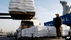 FILE - A South Korean farmer looks at packs of rice for North Korea being loaded onto a ship at Incheon port in Incheon, South Korea.