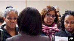 寻找工作的人12月12日在纽约一个招聘会上与招聘人员交谈