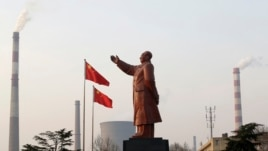 A statue of former Chinese leader Mao Zedong is seen in front of smoking chimneys at Wuhan Iron And Steel Corp in Wuhan, Hubei province, Mar. 6, 2013.