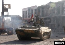 FILE - Syrian troops roll into the center of Qusair June 5, 2013, after capturing the stragegic town with key help from Lebanese Hezbollah fighters.