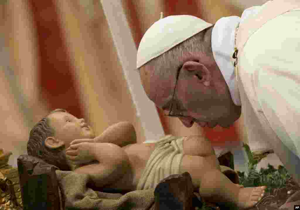 Pope Francis kisses the statue of Baby Jesus as he arrives to celebrate a Mass for families in St.Peter's Basilica at the Vatican.