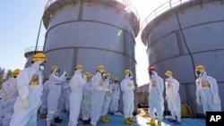PM Jepang Shinzo Abe (tiga dari kanan, mengenakan helm merah) mendapat penjelasan dari pimpinanPLTN Dai-ichi Fukushima Akira Ono (empat dari kanan) saat meninjau wilayah tersebut, 19 September 2013 (Foto: dok). Enam pekerja PLTN Fukushima dilaporkan tersiram air radioaktif, Rabu (9/10).