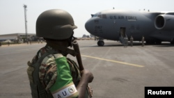An African Union (AU) peacekeeper for the Central African Republic (MISCA) keeps guard as a U.S. Air Force plane lands carrying the first contingent of Rwandan AU soldiers at the capital Bangui January 16, 2014. REUTERS/Siegfried Modola (CENTRAL AFRICAN R