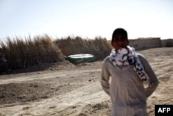 FILE - An Iranian man looks toward an abandoned boat in Sikh Sar village at the Hamoon wetland near the Zabol town in Sistan-Baluchistan province, Feb. 2, 2015.